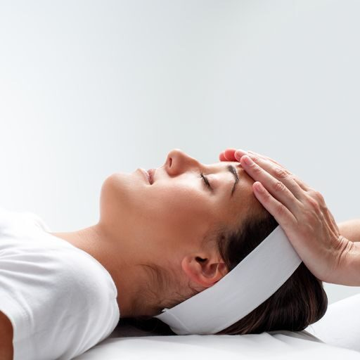 woman-relaxing-at-reiki-session--480118982-5aeda463c5542e0036ccdd4c